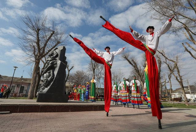 Artists perform near a Soviet-era monument during celebration of Maslenitsa, also known as Pancake Week, which is a pagan holiday marking the end of winter, in Yevpatoriya, Crimea on March 14, 2021. (Photo by Alexey Pavlishak/Reuters)