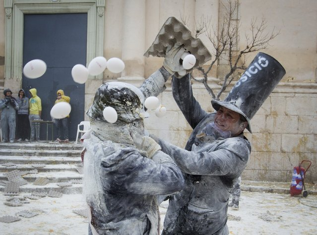 "A reveller throws an egg carton to another participant as they take part in the ""Enfarinats"" battle in the southeastern Spanish town of Ibi on December 28, 2015. During this 200-year-old traditional festival participants known as Els Enfarinats (those covered in flour) dress in mock military clothes and stage a mock coup d'etat as they battle using flour, eggs and firecrackers outside the city town hall as part of the celebrations of the Day of the Innocents. (Photo by Jaime Reina/AFP Photo)"