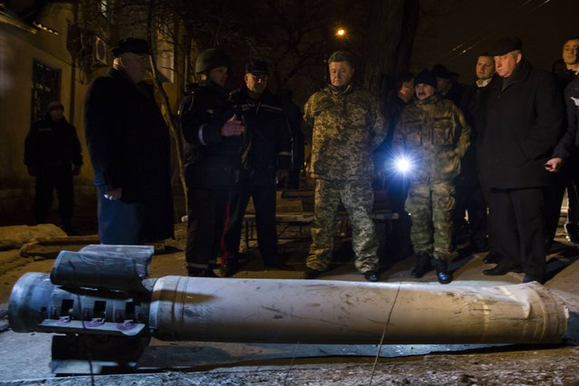 Ukrainian President Petro Poroshenko (front row, C) looks at the remains of ammunition during a visit to Kramatorsk, late February 10, 2015. Rockets killed more than 10 civilians and soldiers deep in Ukrainian government-held territory in Kramatorsk on Tuesday and rebels pushed on with an assault on an army-held rail junction, setbacks that showed Kiev's position worsening on the eve of peace talks. (Photo by Mikhail Palinchak/Reuters/Ukrainian Presidential Press Service)