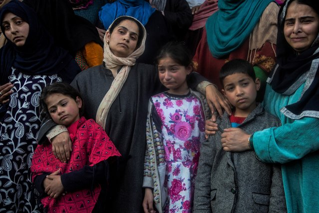 Wife and children wail near the coffin of elected official Riyaz Ahmad during his funeral in Sopore, 55 kilometers (34 miles) north of Srinagar, Indian controlled Kashmir, Monday, March. 29, 2021. Gunmen killed an elected official of India's ruling party and a policeman in disputed Kashmir on Monday, police said. Police blamed anti-India militants for the attack. None of the rebel groups that have been fighting against Indian rule since 1989 immediately claimed responsibility for the attack. (Photo by Mukhtar Khan/AP Photo).