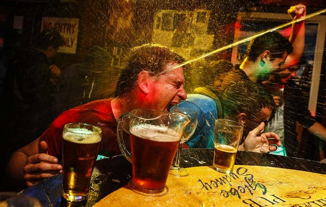 """A party goer is splashed with water after winning a crab race at a pub called the """"Friend in Hand"""" in  Sydney, Australia, on August 21, 2013. (Photo by Daniel Munoz/Reuters)"""