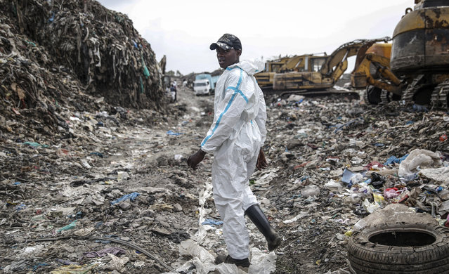 Isaac Kivai scavenges recyclable materials for a living at Dandora, the largest garbage dump in the Kenyan capital of Nairobi, Sunday, March 28, 2021. He wears a protective medical suit he and his friends had found in the trash. The waste pickers say the gear protects them from the weather during the rainy season. (Photo by Brian Inganga/AP Photo)
