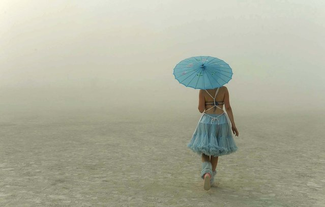 A young woman walks through the dusty playa. (Photo by Andy Barron/The Reno Gazette-Journal)