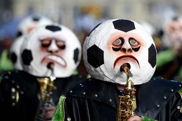 Masked revelers parade through the streets during the start of the carnival season in Lucerne, Switzerland, 12 February 2015. (Photo by Urs Flueeler/EPA)