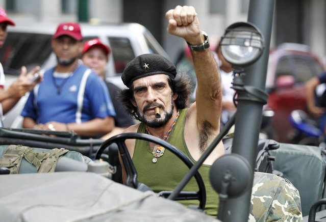 "Humberto Lopez, known as ""El Che"", a supporter of Venezuela's officialism, gestures as he drives his jeep some streets away from the building housing the National Assembly in Caracas, January 5, 2016. (Photo by Christian Veron/Reuters)"