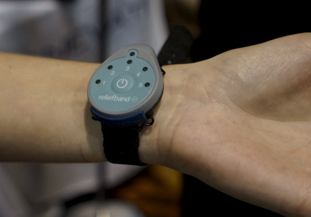 An attendee tries the ReliefBand wearable electronic device, described as used to treat nausea and vomiting associated with motion sickness and pregnancy, during the opening event at the Consumer Electronics Show in Las Vegas January 4, 2016. (Photo by Rick Wilking/Reuters)