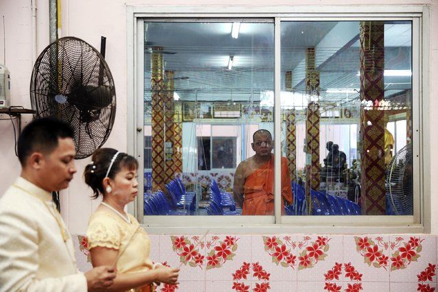 A Buddhist monk looks at a bride and a groom before they step into a pink coffin during their wedding ceremony at Wat Takien temple in Nonthaburi province, on the outskirts of Bangkok February 14, 2015. (Photo by Damir Sagolj/Reuters)
