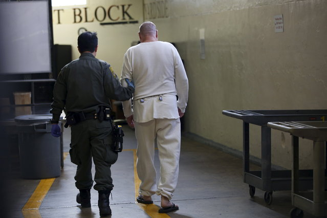A guard escorts a condemned inmate down a corridor in the East Block during a media tour of California's Death Row at San Quentin State Prison in San Quentin, California December 29, 2015. (Photo by Stephen Lam/Reuters)