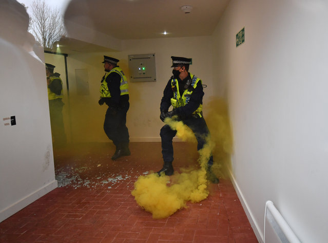 Police officers deal with a flare that was thrown through a window as United fans protest about the owners of the club, before the Premier League match between Manchester United and Liverpool at Old Trafford on May 2, 2021 in Manchester, United Kingdom. Sporting stadiums around the UK remain under strict restrictions due to the Coronavirus Pandemic as Government social distancing laws prohibit fans inside venues resulting in games being played behind closed doors. (Photo by Anthony Devlin/Offside via Getty Images)
