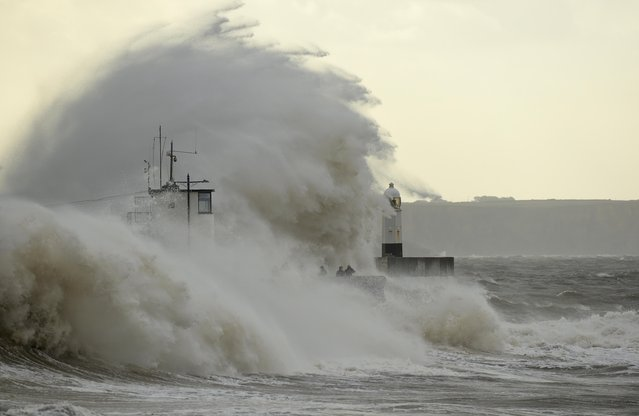 Waves crash over the lighthouse at Porthcawl, South Wales, Britain on August 21, 2020. (Photo by Rebecca Naden/Reuters)