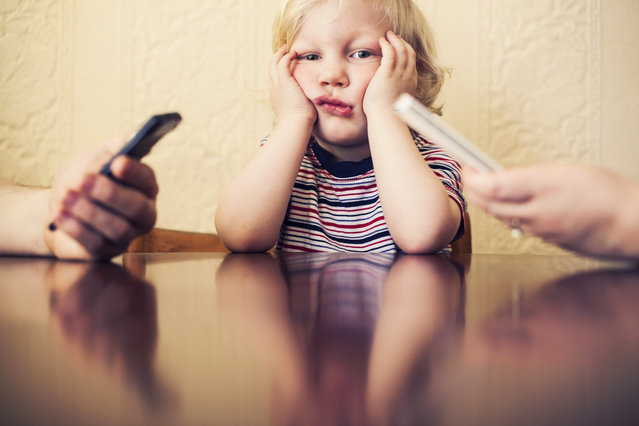 Little boy sitting and looking bored while his parents are busy using their smart phones. (Photo by Sally Anscombe/Getty Images)