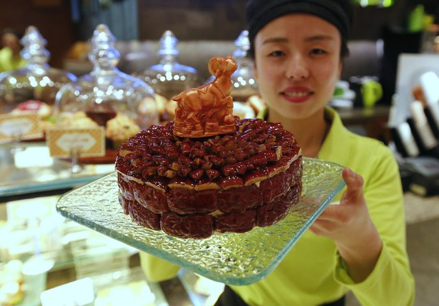 A waitress poses with a cake decorated with a goat-shaped chocolate, which is painted with edible gold powder, to celebrate the upcoming Chinese Lunar New Year, during a photo opportunity at a bakery of Kerry Hotel in Beijing, February 12, 2015. (Photo by Kim Kyung-Hoon/Reuters)