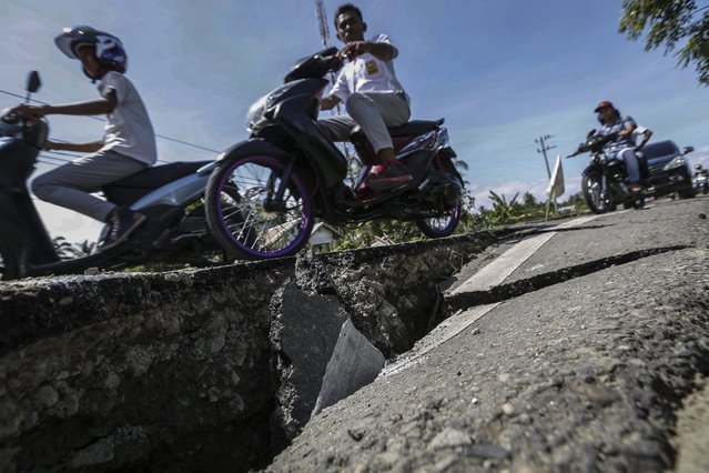 Indonesian motorists ride pass a crack in the road after an earthquake struck Pidie Jaya, Aceh, Indonesia, 07 December 2016. (Photo by Hotli Simanjuntak/EPA)