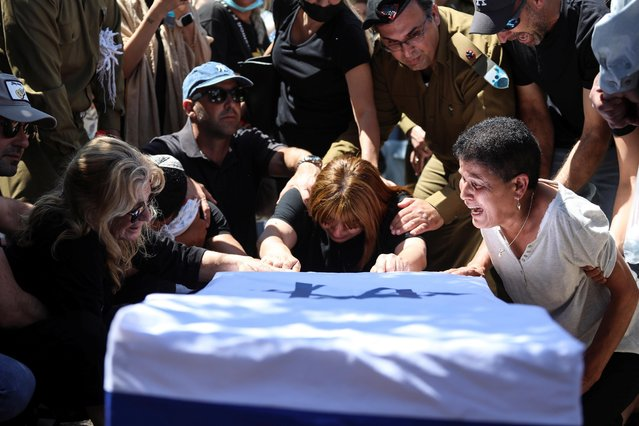 Family and friends, including Israeli soldiers, mourn over the flag-covered coffin of Israeli soldier Omer Tabib, at his funeral in Eliakim, Israel, May 13, 2021. (Photo by Avishag Shar-Yashuv/Reuters)