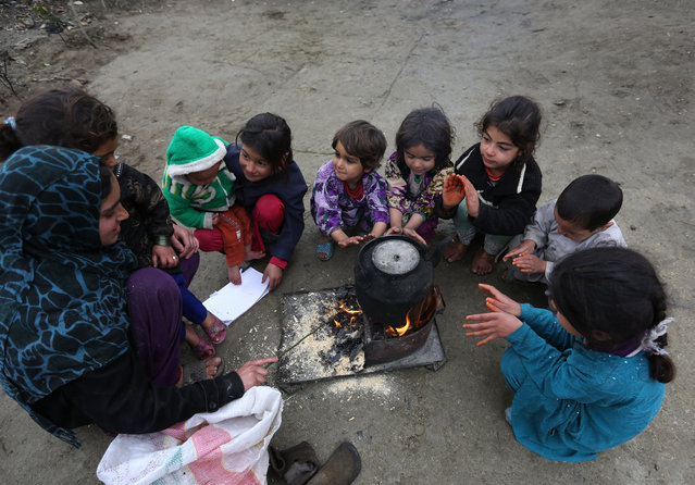 Afghan children warm themselves near a cooking fire on the outskirts of Kabul, Afghanistan, Saturday, February 21, 2015. (Photo by Rahmat Gul/AP Photo)