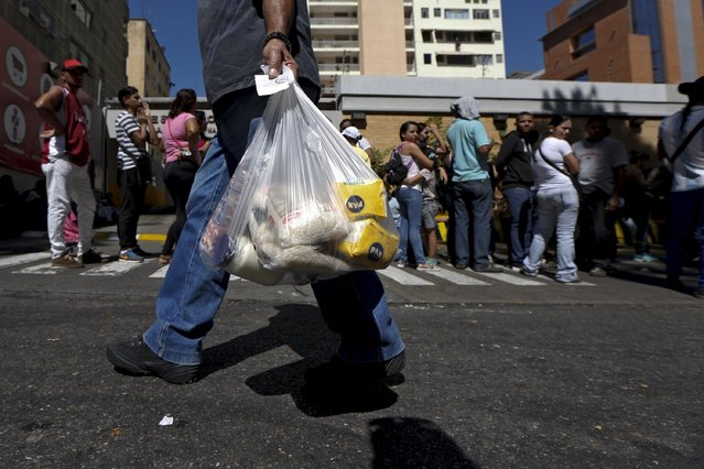 A man walks out of a supermarket carrying corn flour, rice and mayonnaise in a plastic bag, while others wait in line to try to buy staple items in Caracas January 16, 2016. (Photo by Carlos Garcia Rawlins/Reuters)