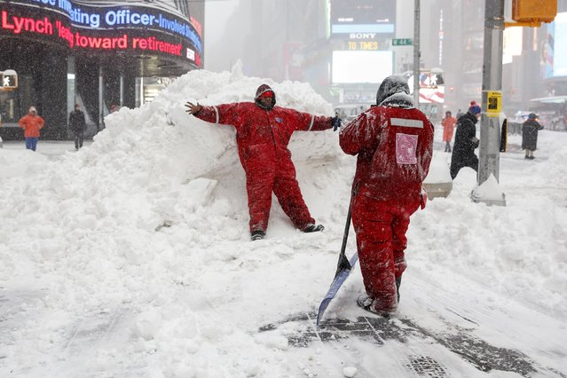 Members of the Times Square Alliance snow clearing team take a photo on a snowbank at Times Square in the Manhattan borough of  New York January 23, 2016. A winter storm dumped nearly 2 feet (58 cm) of snow on the suburbs of Washington, D.C., on Saturday before moving on to Philadelphia and New York, paralyzing road, rail and airline travel along the U.S. East Coast. (Photo by Shannon Stapleton/Reuters)