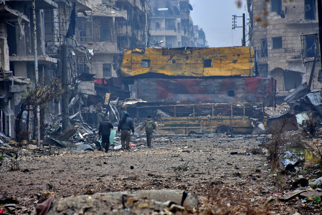 Syrian pro-government forces walk in Aleppo's Bustan al-Qasr neighbourhood after they captured the area in the eastern part of the war torn city on December 13, 2016. After weeks of heavy fighting, regime forces were poised to take full control of Aleppo, dealing the biggest blow to Syria's rebellion in more than five years of civil war. (Photo by George Ourfalian/AFP Photo)