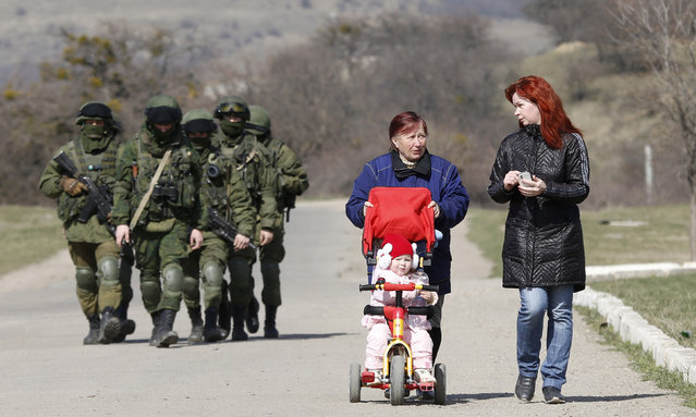 Women talk as they take a walk with a child in a pram while armed men, believed to be Russian servicemen, follow them outside a Ukrainian military base in Perevalnoye, near Simferopol, March 14, 2014. (Photo by Vasily Fedosenko/Reuters)