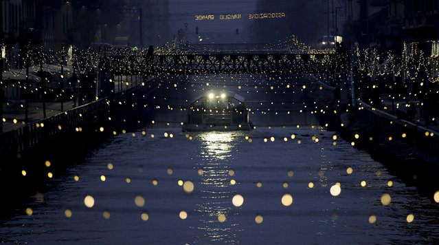 A tourist boat sail as Christmas lights illuminate the Darsena dei Navigli, the neighborhood named for the canals that run through this area of Milan, Italy, Monday, December 12, 2016. (Photo by Luca Bruno/AP Photo)