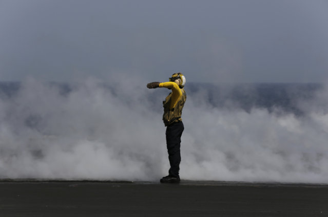 A U.S. sailor guides a military jet preparing for takeoff just after another has catapulted off the deck of the USS Carl Vinson aircraft carrier in the Persian Gulf, Thursday, March 19, 2015. (Photo by Hasan Jamali/AP Photo)