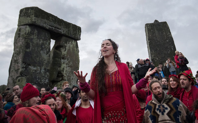 """Members of the Shakti Sings choir sing as druids, pagans and revellers gather in the centre of Stonehenge, hoping to see the sun rise, as they take part in a winter solstice ceremony at the ancient neolithic monument of Stonehenge near Amesbury on December 21, 2016 in Wiltshire, England. Despite a forecast for cloud and rain, a large crowd gathered at the famous historic stone circle, a UNESCO listed ancient monument, to celebrate the sunrise closest to the Winter Solstice, the shortest day of the year. The event is claimed to be more important in the pagan calendar than the summer solstice, because it marks the """"re-birth"""" of the Sun for the New Year. (Photo by Matt Cardy/Getty Images)"""