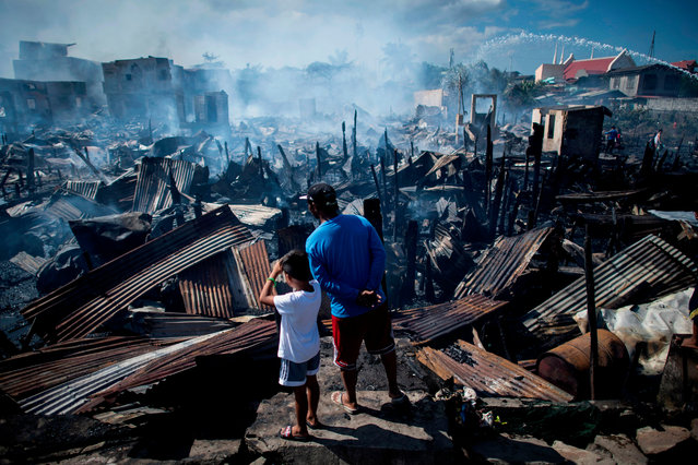Residents look at destroyed houses after a fire engulfed a slum area in Navotas along Manila Bay on November 8, 2018. Some 150 families were affected by the fire, according to local media reports. (Photo by Noel Celis/AFP Photo)