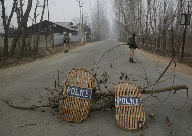 Indian soldiers stand guard next to a road blockade using tree branches and wooden shields near the site of a gun-battle in Mujagund area some 25 Kilometers (16 miles) from Srinagar, Indian controlled Kashmir, Sunday, December 9, 2018. Indian troops killed three suspected rebels in the outskirts of disputed Kashmir's main city ending nearly 18-hour-long gunbattle, officials said Sunday. (Photo by Mukhtar Khan/AP Photo)