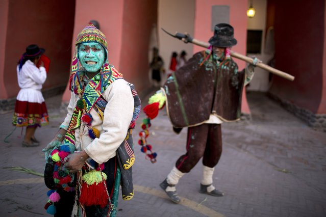 In this Sunday, March 29, 2015 photo, a man, who dons traditional dress from the Huanta district of Ayacucho, smiles after performing in the Vencedores de Ayacucho dance festival, at the Acho bullring in Lima, Peru. (Photo by Rodrigo Abd/AP Photo)