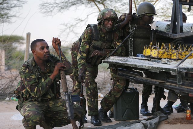 Kenyan soldiers take cover as heavy gunfire continues in front of Garissa University in Garissa town, located near the border with Somalia, some 370km northeast of the capital Nairobi, Kenya, 02 April 2015. The government said 70 people have been killed and 79 others have been injured in an attack carried out by Somalia's Islamist militant group al-Shabab. (Photo by Dai Kurokawa/EPA)