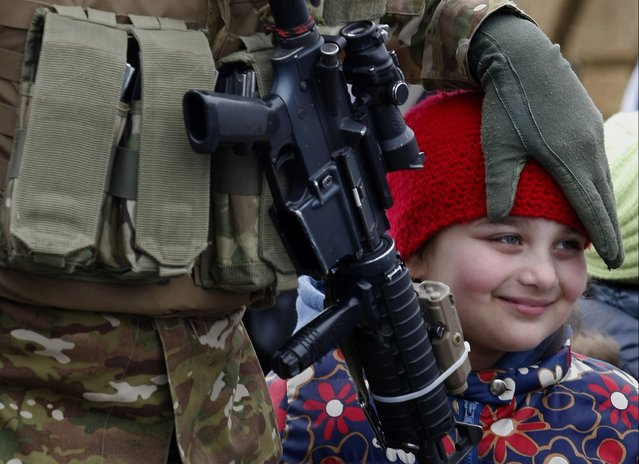 A Georgian soldier touches the head of his daughter during a sending off ceremony before leaving for Afghanistan in Tbilisi, Georgia, Tuesday, March 24, 2015. Georgian troops will take part in the NATO peace support mission in Afghanistan. (Photo by Shakh Aivazov/AP Photo)
