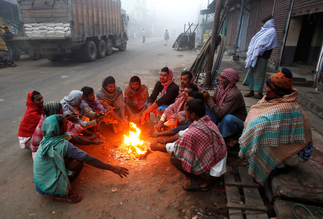 Labourers warm themselves up by a bonfire on a road at a market on a foggy morning on the outskirts of Agartala, January 6, 2017. (Photo by Jayanta Dey/Reuters)