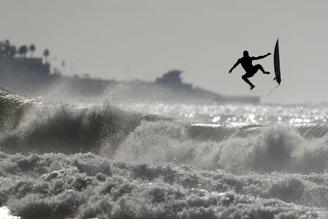 A surfer exits a wave while surfing at Black's Beach Tuesday, December 18, 2018, in San Diego. Large surf continued to pound the California coast Tuesday, as officials warned of dangerous currents along the beaches and hazardous conditions at sea. (Photo by Gregory Bull/AP Photo)