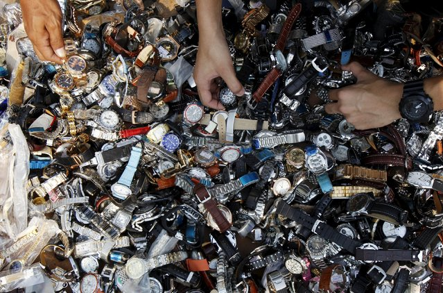 Thai officials inspect counterfeit watches before destroying them at Khlongluang Transportation Station in Pathumtani province, on the outskirts of Bangkok April 9, 2015. (Photo by Chaiwat Subprasom/Reuters)
