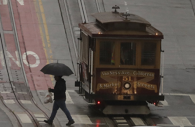 A pedestrian walks in the rain in front of a cable car in San Francisco, Wednesday, January 16, 2019. A series of storms dropped rain up and down the state and snow in mountain regions this week, but the latest storm could be the strongest that Northern California has seen so far this year. (Photo by Jeff Chiu/AP Photo)