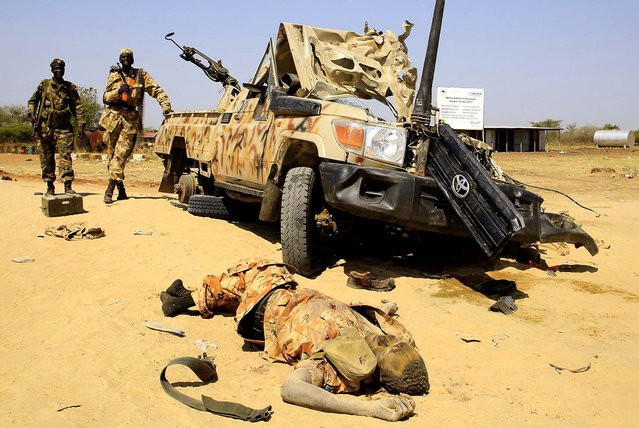 The body of a dead rebel killed by South Sudan army soldiers during a gunfight lies next to a destroyed military truck near Bor Airport, 108 miles northwest of the capital Juba, on December 25, 2013. South Sudanese troops have retaken the flashpoint town of Bor in Jonglei state, a week after the town fell to rebels loyal to rebel leader Riek Machar. (Photo by James Akena/Reuters)