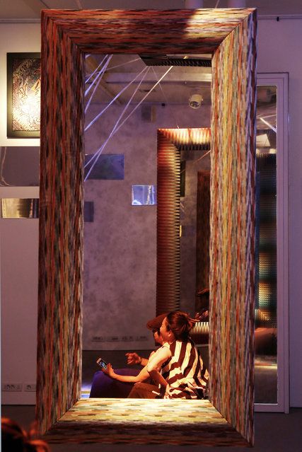 In this picture taken on Wednesday, April 15, 2015 people sit next to a mirror by Missoni at the Milan Furniture Fair, in Milan, Italy. (Photo by Antonio Calanni/AP Photo)