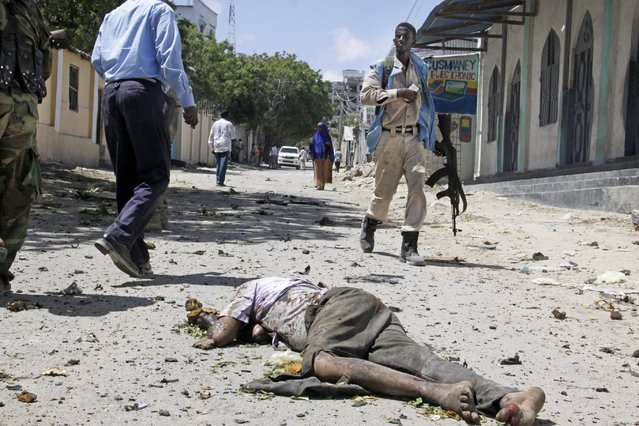 A Somali soldier walks past the body of a civilian lying in the street after a car bomb detonated at the gates of a government office complex in the capital Mogadishu, Somalia Tuesday, April 14, 2015. A number of people were killed on Tuesday when attackers stormed the ministry of higher education after a suicide car bomber detonated his vehicle at the gate of the office complex, opening the way for gunmen to enter, according to a senior police officer. (Photo by Farah Abdi Warsameh/AP Photo)