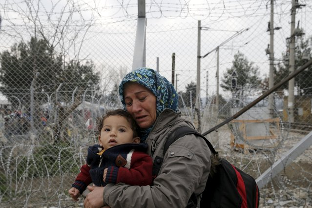 A migrant holding a child cries next to a border fence at the Macedonian-Greek border in Gevgelija, Macedonia February 24, 2016. (Photo by Marko Djurica/Reuters)