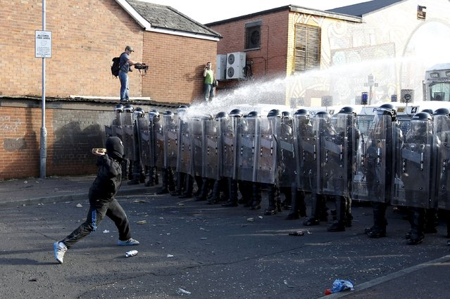 Nationalist youths and police in riot gear clash in the Ardoyne area of north Belfast, in this July 12, 2011 file photo. (Photo by Cathal McNaughton/Reuters)