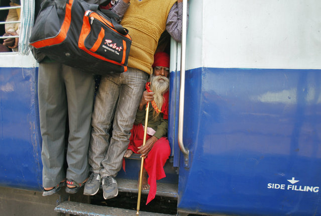 A Sadhu or a Hindu holyman sits at the door of an overcrowded passenger train after boarding, at a railway station in the northern Indian city of Allahabad, February 11, 2013. (Photo by Jitendra Prakash/Reuters)
