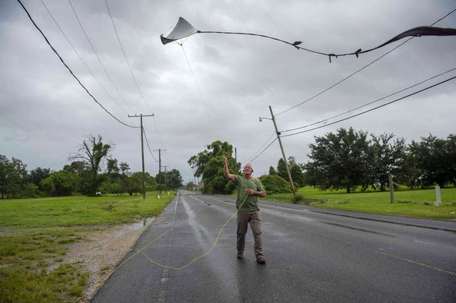 John Kain, 62, of Arabi, tries to fly a kite in Hurricane Ida winds with a kite he just made out of a political campaign sign on Sunday, August 29, 2021. (Photo by Chris Granger/The Advocate via AP Photo)