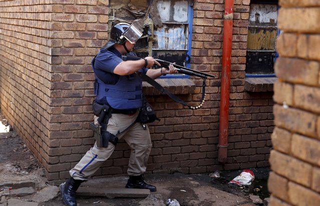 A police officer takes aim as they search a hostel in Actonville,east of  Johannesburg, April 16, 2015. South African police fired rubber bullets and tear gas on Thursday to disperse a crowd of anti-immigrant protesters in an eastern suburb of Johannesburg, the country's biggest commercial city, a Reuters witness said. (Photo by Siphiwe Sibeko/Reuters)