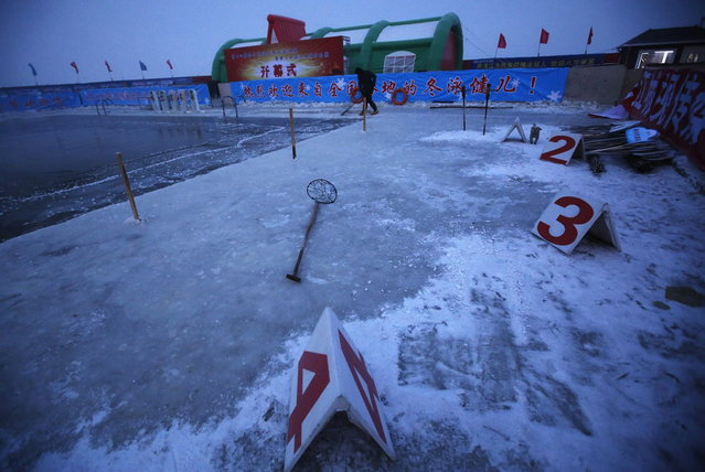 A worker breaks ice on a pool carved into the thick ice covering the Songhua River in the early morning as he prepares the Harbin Ice Swimming Competition in the northern city of Harbin, Heilongjiang province January 5, 2014. (Photo by Kim Kyung-Hoon/Reuters)