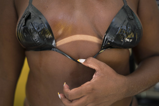 In this January 15, 2017 photo, a woman shows her crisp tan line, underneath a bikini made of black electrical tape at the Erika Bronze rooftop salon in the suburban neighborhood of Realengo in Rio de Janeiro, Brazil. Clients must book and pay about $20 in advance to guarantee a spot on one of the terrace lounges. (Photo by Renata Brito/AP Photo)