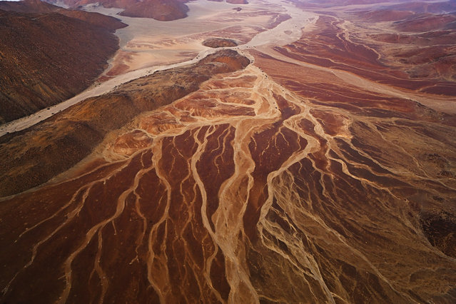 An aerial view of mountains and dry creek beds near Messum Crater, in October, 2014, in the Namib Desert, Namibia. (Photo by Theo Allofs/Barcroft Media)