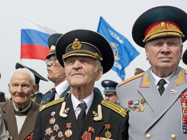 Russian veteran Nikolai Mihalovic Beljajev, 92, center, stands besides other Russian veterans during the 70th anniversary celebrations of the so-called Elbe Day in Torgau, eastern Germany, Saturday, April 25, 2015. The WW II link-up of US and Soviet Forces occurred here at the river Elbe on April 25, 1945. (Photo by Jens Meyer/AP Photo)