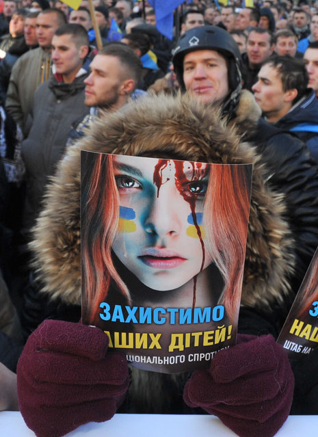"""A protester holds a poster against police violence reading """"Protect our Children"""" during a rally in front of Ukrainian parliament on December 3, 2013. (Photo by Genya Savilov/AFP Photo)"""