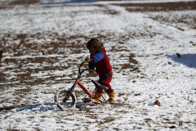 A child plays with a bicycle on snow in al-Rai town, northern Aleppo countryside, Syria January 28, 2017. (Photo by Khalil Ashawi/Reuters)
