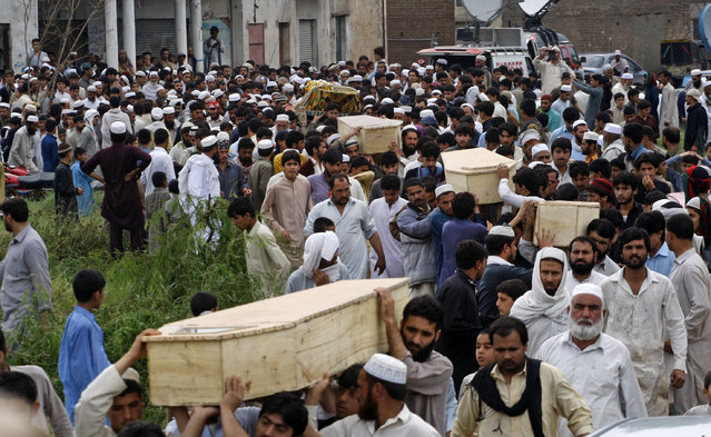 Pakistani villagers carry coffins of victims killed from heavy rain and windstorm that reached up to a speed of 120 kph (75 mph) Sunday evening which collapsed hundreds of buildings, uprooted trees, and electric poles, in Peshawar, Pakistan, Monday, April 27, 2015. Officials say death toll has risen to at least 44. (Photo by Mohammad Sajjad/AP Photo)